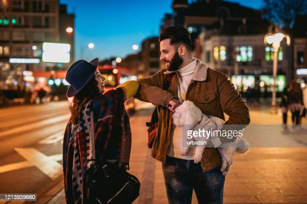young couple greeting during virus pandemic - elbow bump stock pictures, royalty-free photos & images
