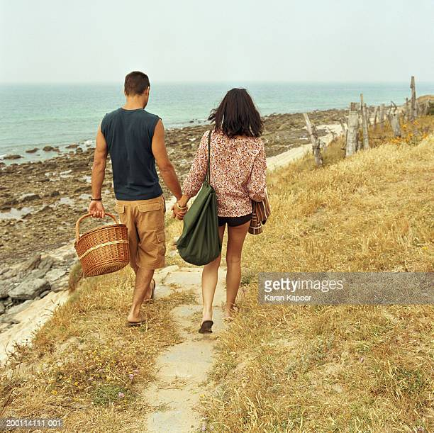 Young couple hand in hand, man carrying picnic basket, rear view