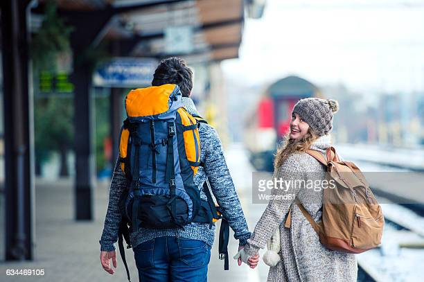 Young couple hand in hand on station platform