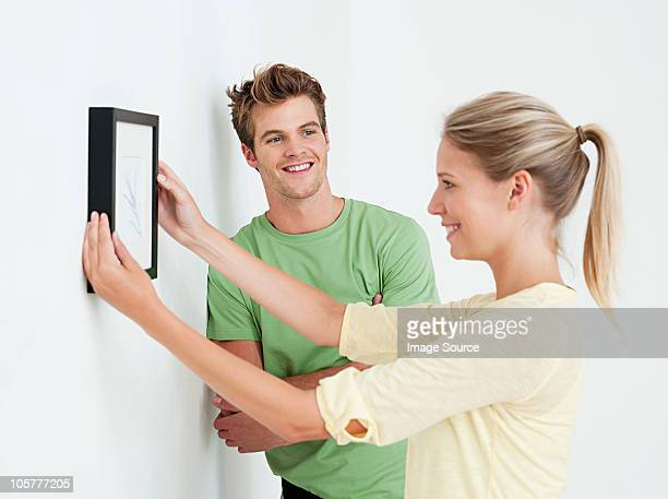Young couple hanging a picture