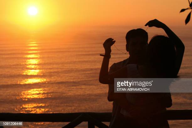 A young couple have a cuddle while watching the sunset in the 'Park of Love' in Lima 14 February 2006 during Valentine's Day AFP PHOTO/EITAN...