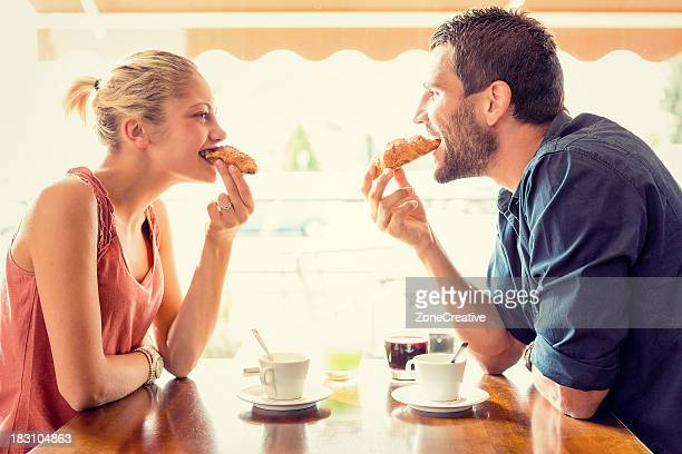 young couple have breakfast at italian café - man eating woman out stock photos and pictures
