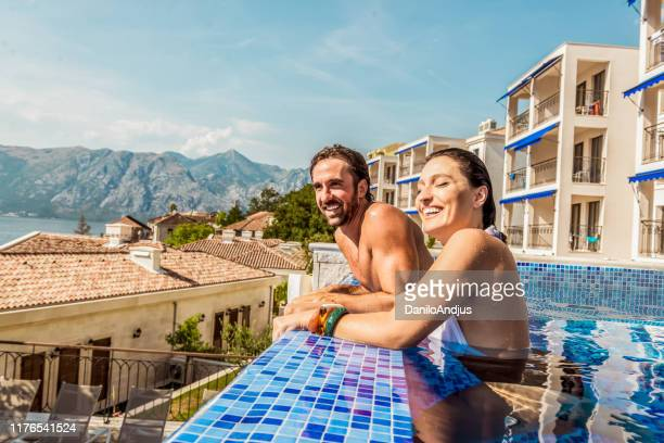 young couple have fun in a pool - geographical locations stock pictures, royalty-free photos & images