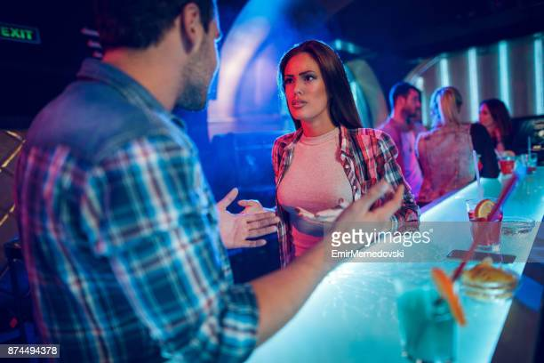 young couple having a big quarrel in the nightclub - women fight stock photos and pictures