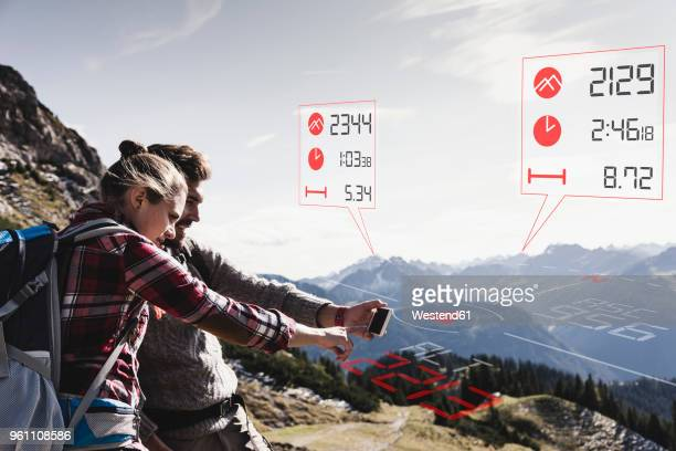 Young couple having a break from hiking checking data emerging from tracker