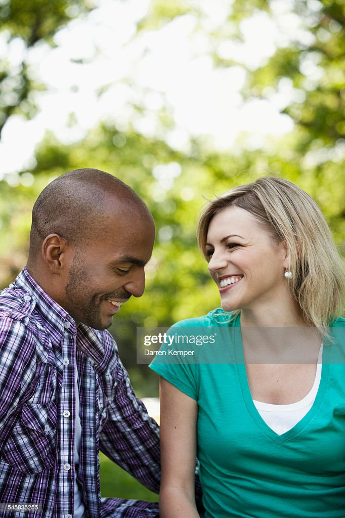 Young couple having a chat in a park : Stock Photo