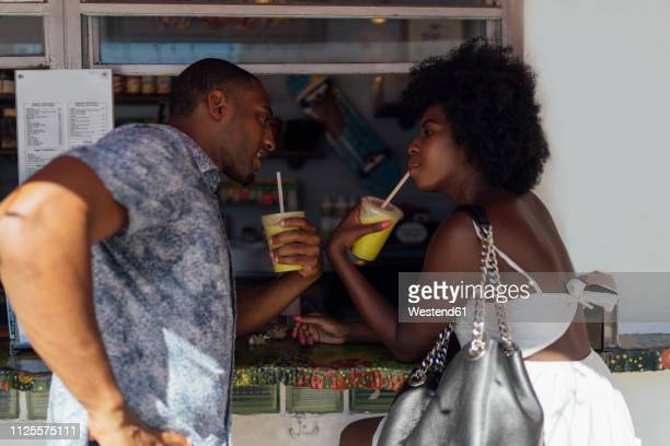 young couple having a drink at a kiosk - miami beach stock pictures, royalty-free photos & images