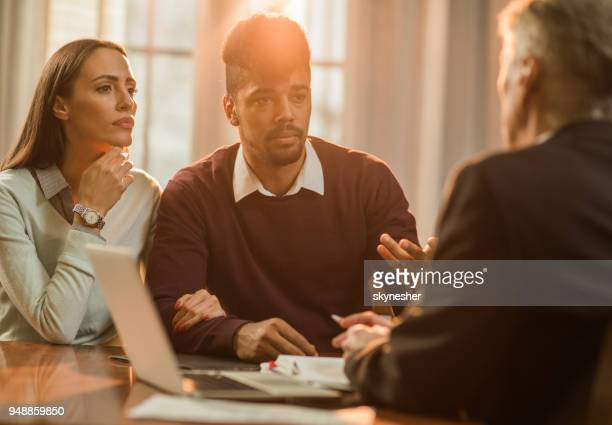 young couple having a meeting with their insurance agent in the office. - banker stock photos and pictures