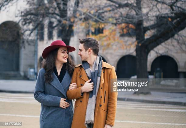 young couple having a pleasant walk in the city - coat stock pictures, royalty-free photos & images
