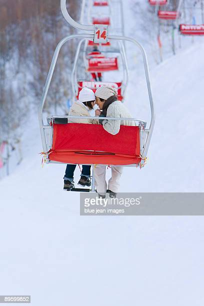 Young couple having a romantic moment on a ski lift
