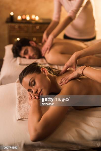 jeune couple ayant massage du dos au cours de leur traitement de spa. - massage couple photos et images de collection