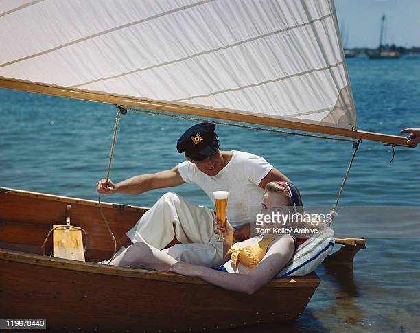 Young couple having beer in sailing boat