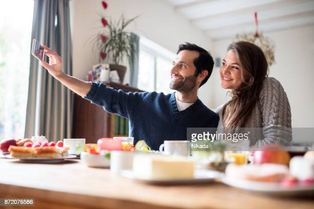 young couple having breakfast and taking a selfie