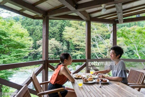 a young couple having breakfast happily in the veranda of the cottage. - コテージ ストックフォトと画像