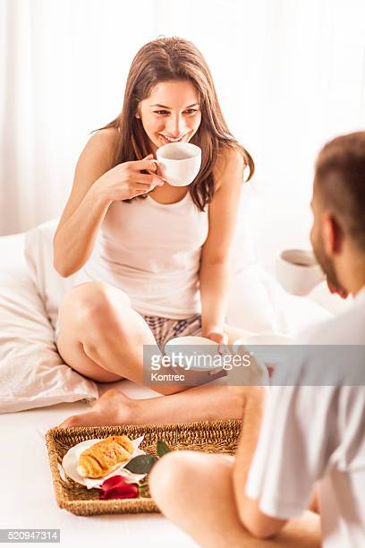Junges Paar mit Frühstück im Bett