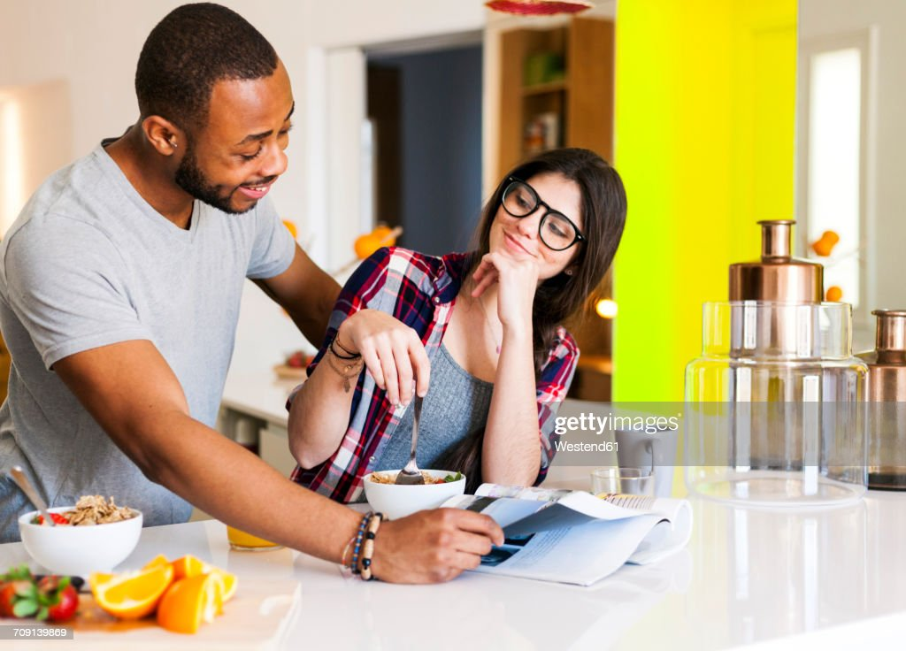 Young couple having breakfast in the kitchen and reading magazine : Stock Photo