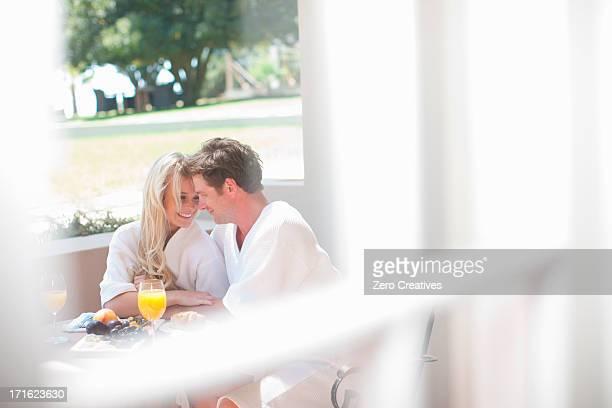 Young couple having breakfast on patio