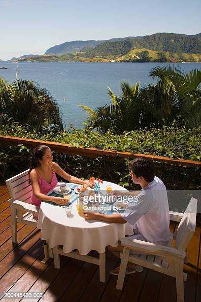 Young couple having breakfast on terrace over bay, elevated view