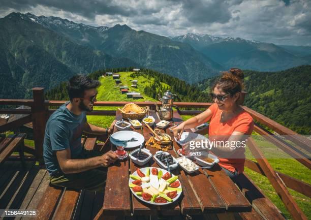 若いカップルは、ポクト高原、カムルヘムシン、リゼ、トルコの黒海地域で風景を眺めた朝食をとっています - トラブゾン ストックフォトと画像