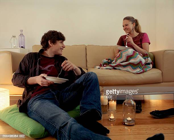 Young couple  having candlelight dinner in living room, smiling