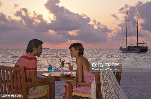 young couple having cocktails near beach, sunset - caroline roux photos photos et images de collection