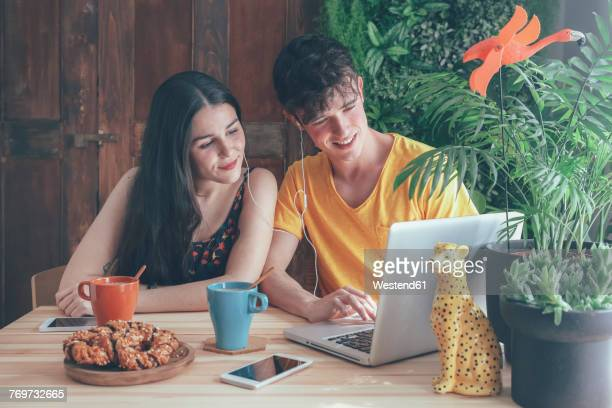 young couple having coffee and chocolate braids using laptop at home - adult film foto e immagini stock
