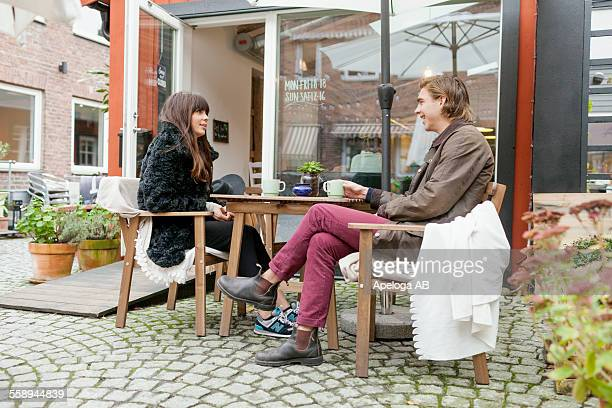 Young couple having coffee at cafe backyard