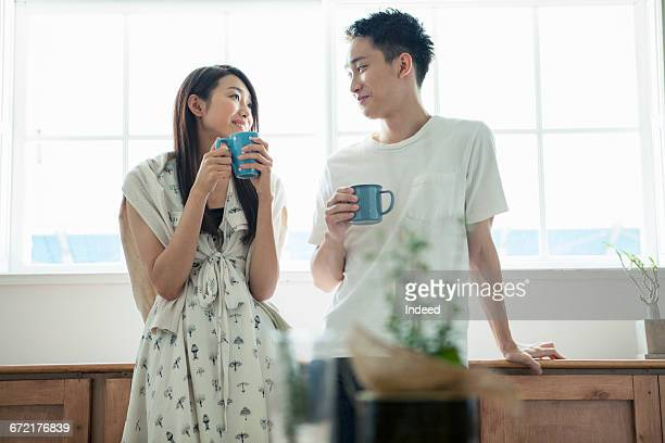 Young couple having coffee by window