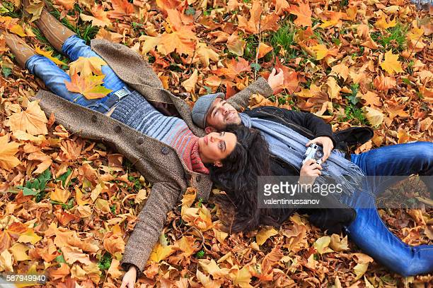 Young couple having fun and lying down on leaves