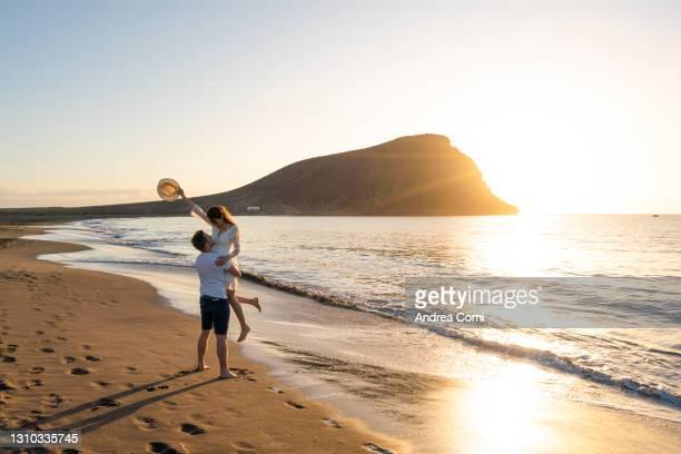 young couple having fun at beach la tejita, tenerife, canary islands - europa meridionale foto e immagini stock
