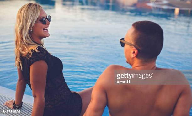 Young couple having fun by the swimming pool