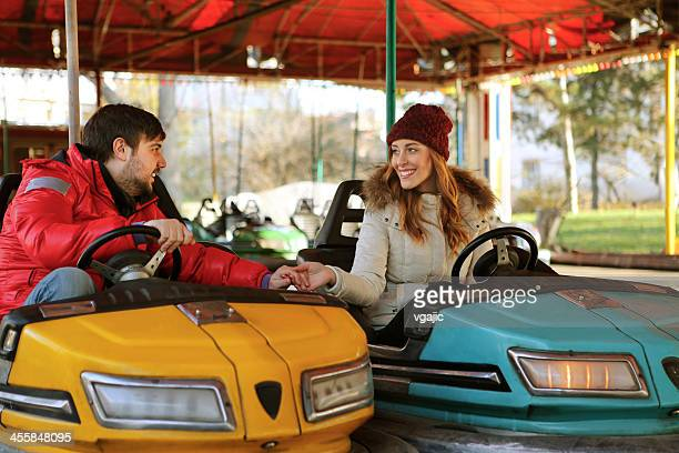 Young Couple Having Fun Driving Bumper Cars.