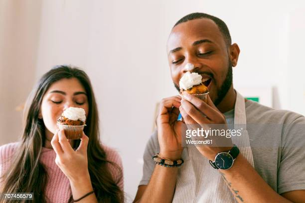 young couple having fun, eating fresh cupcakes - indulgence stock pictures, royalty-free photos & images
