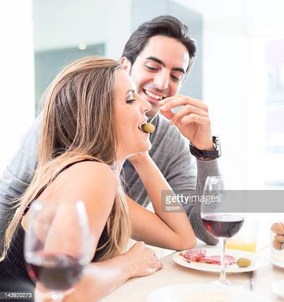 Junges Paar, die Spaß in olives restaurant, Essen und trinken Wein.