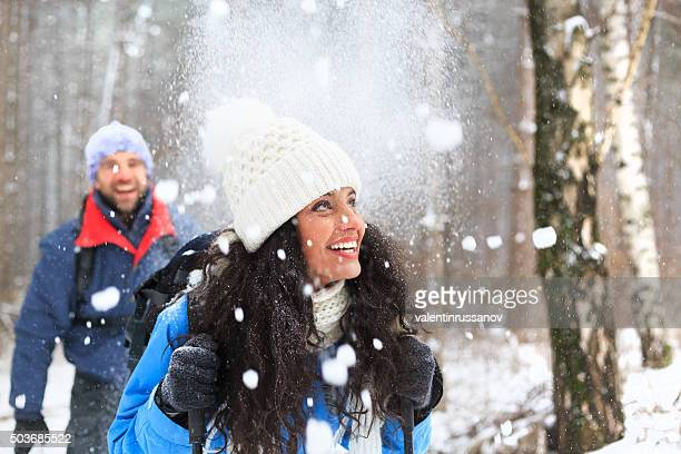 Young couple having fun in the winter forest