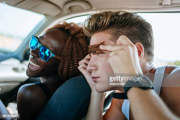 Young couple having fun inside a car
