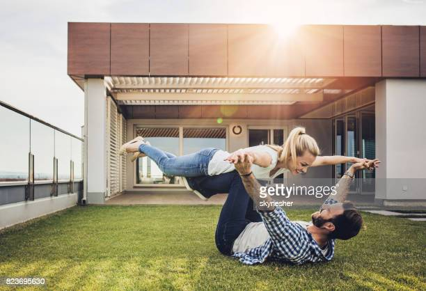 young couple having fun on a terrace in front of a penthouse. - women of penthouse stock photos and pictures