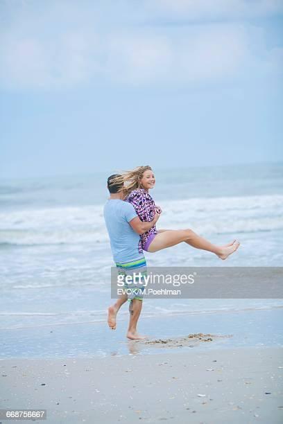 Young couple (16-17) having fun on beach