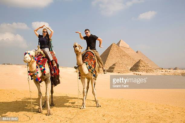 young couple having fun on camel near pyramids