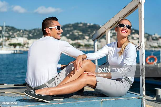 pareja joven divirtiéndose en el muelle en el puerto - traje deportivo fotografías e imágenes de stock