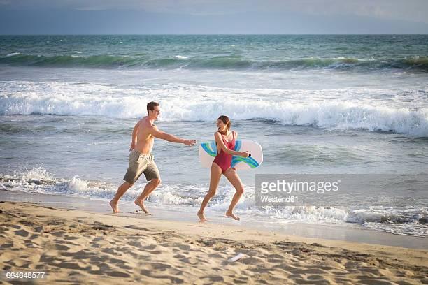 young couple having fun on the beach - 鬼ごっこ ストックフォトと画像