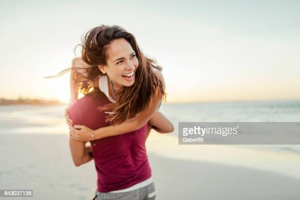 young couple having fun on the beach - candid beach stock photos and pictures