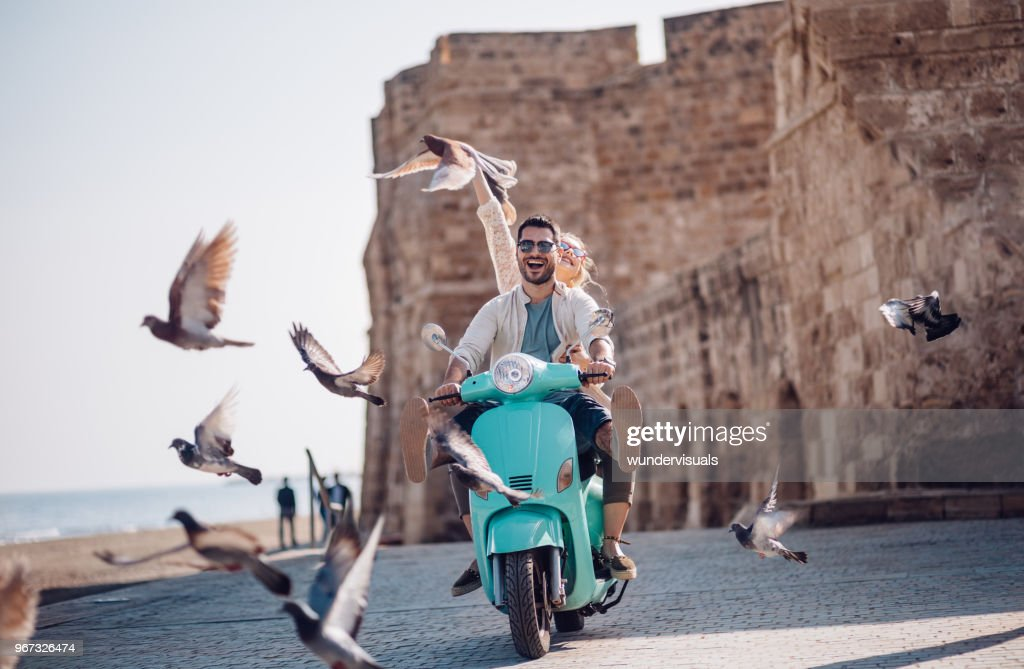 Young couple having fun riding scooter in old European town : Stock Photo