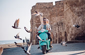Young couple having fun riding scooter in old European town