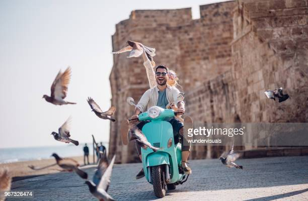 young couple having fun riding scooter in old european town - vacanze foto e immagini stock