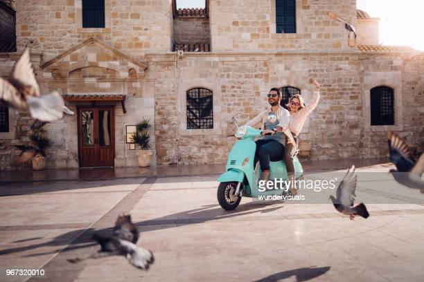 Young couple having fun riding vintage scooter in European town