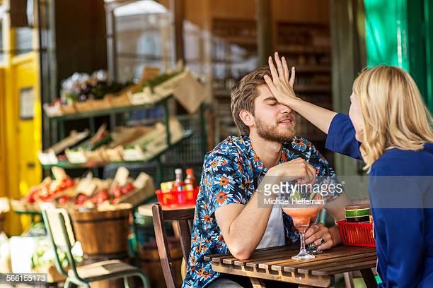 Young couple having fun sitting outside bar