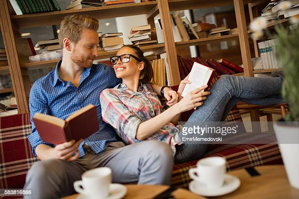 Young couple having fun while reading books in library.