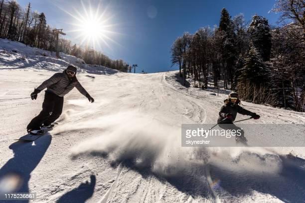 pareja joven divirtiéndose mientras esquiaba por la ladera. - sólo con adultos fotografías e imágenes de stock