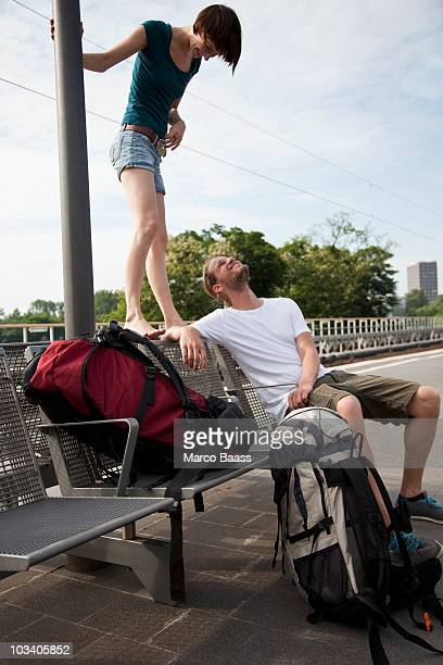 A young couple having fun while waiting on a train platform